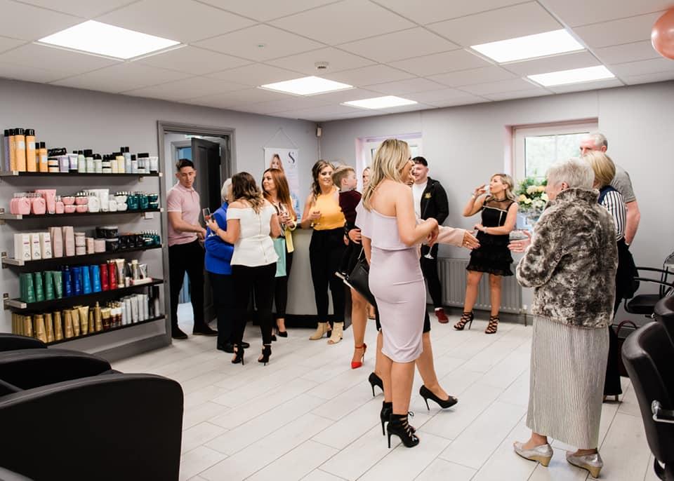 group of people inside Prestige Hair Design salon